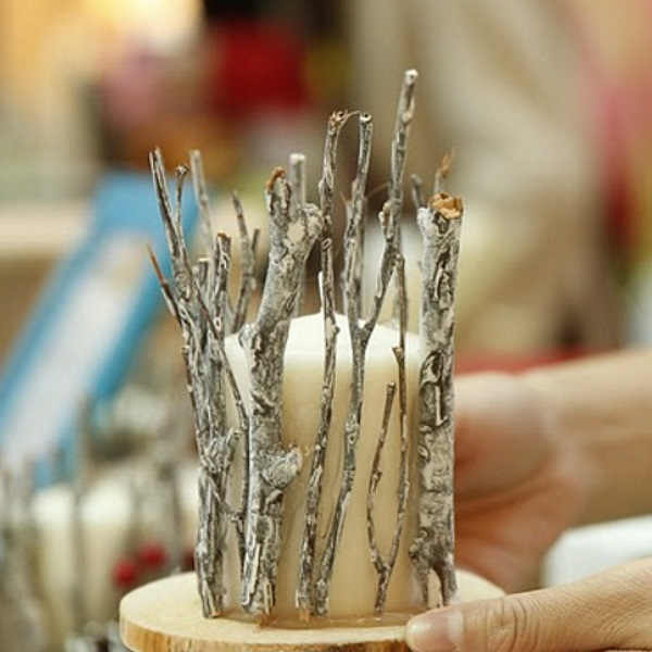 Decorate candles with silver and glitter twigs.